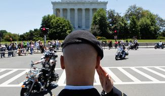 """Motorcycles drive past the Lincoln Memorial as Colin Morris, of the US Army, salutes during the annual Rolling Thunder """"Ride for Freedom"""" parade ahead of Memorial Day in Washington, Sunday, May 26, 2013. (AP Photo/Molly Riley)"""