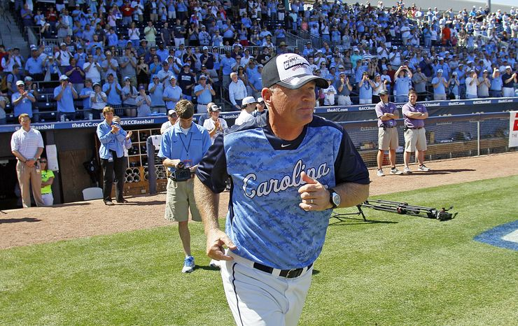 North Carolina head coach Mike Fox takes the field to accept the championship trophy following Carolina's 4-1 win over Virginia Tech in an Atlantic Coast Conference NCAA college baseball game on Sunday, May 26, 2013, in Durham, N.C. (AP Photo/Karl B DeBla