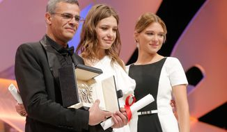 """From left, director Abdellatif Kechiche, actors Adele Exarchopoulos and Lea Seydoux react after they received the Palme d'Or award for the film """"La Vie D'Adele"""" during an awards ceremony at the 66th international film festival, in Cannes, southern France, Sunday, May 26, 2013. (Photo by Todd Williamson/Invision/AP)"""