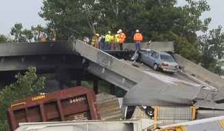 Emergency personnel respond to the scene of a train derailment near Rockview, Mo., on Saturday, May 25, 2013. The National Transportation Safety Board has launched an investigation into the cause of a cargo train collision that partially collapsed a highway overpass in southeast Missouri, injuring seven people. (AP Photo/The Southeast Missourian, Fred Lynch)