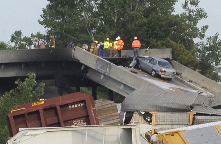 Emergency personnel respond to the scene of a train derailment near Rockview, Mo., on Saturday, May 25, 2013. The National Transportation Safety Board has launched an investigation into the cause of a cargo train collision that partially collapsed a highway overpass in southeast Missouri, injuring seven people. (AP