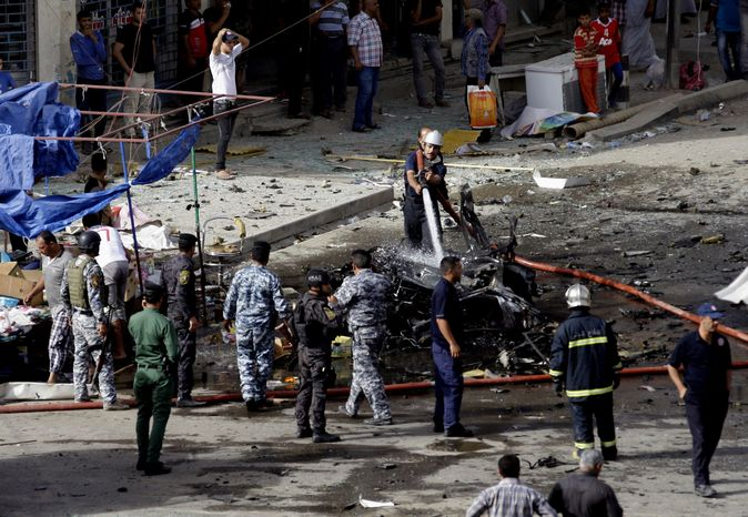 Security forces inspect the scene of a car bomb attack in the Baghdad, Iraq, Monday, May 27, 2013. A parked car bomb explosion in the busy commercial Sadoun Street i