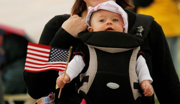 Cora Jacoby, six-months old, of Fond du Lac, Wisc., waves her flag during the Memorial Day parade in West Bend on Monday, May 27, 2013. (AP Photo/The Daily News, John Ehlke)