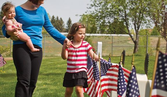 Five-year-old Lydia Slade straightens a flag among the grave markers of Greenhill Cemetery Monday, May 27, 2013 after the Memorial Day Service while walking along with her mother, Anna who is carrying her sister Jenna. (AP Photos/Laramie Boomerang, Jeremy Martin)