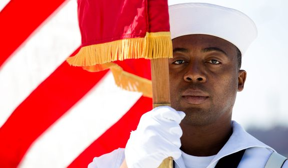 Seaman Daniel Odoi of the Navy Operational Support Center of New York City presents the American flag during a Memorial Day wreath laying at the Franklin D. Roosevelt Four Freedoms Park on Roosevelt Island, Monday, May 27, 2013, in New York. (AP Photo/John Minchillo)