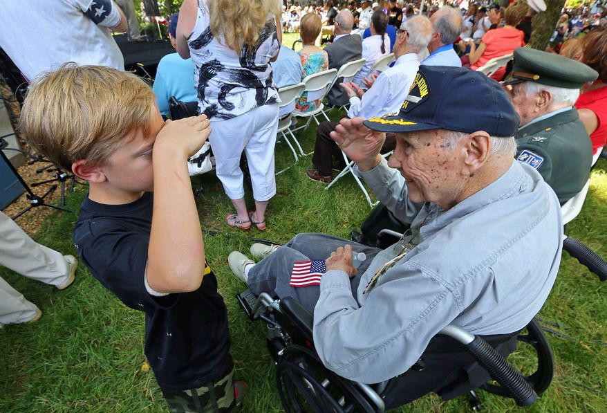 "Eight-year-old Jackson Turman of Woodstock, Ga., gives WWII Navy Veteran and Vietnam Veteran Frank Coleman, 85, Roswell, a salute during the ""Roswell Remembers"" Memorial Day military ceremony at city hall on Monday, May 27, 2013, in Roswell, Ga. Mr. Coleman returned the salute and gave the young man a hug. Jackson was attending the Memorial Day service with his grandfather Russ Johnson, of Roswell, who is a Marine Vietnam veteran.  (AP Photo/Atlanta Journal Constitution, Curtis Compton)"