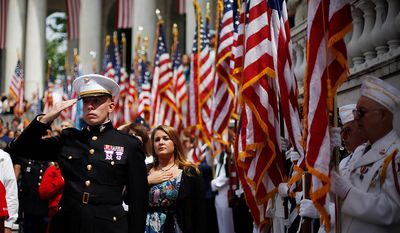 U.S. Marine Corps, 2nd Lt. Adam Carroll, left, pays tribute as he salutes during the playing of the National Anthem at the Memorial Day ceremony in the Memorial Amphitheater at Arlington National Cemetery Monday, May 27, 2013, in Arlington, Va. (AP Photo/Pablo Martinez Monsivais)