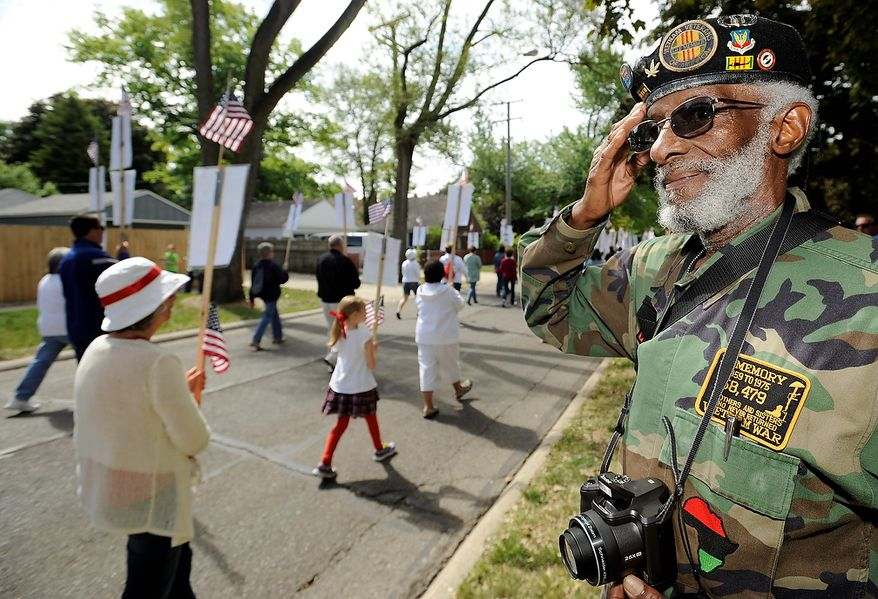 Staff Sgt. Edgar A. Feagines,of Ferndale, who was in the Air Force from 1959-70 and served in Vietnam, salutes Michigan's Fallen Foot Float in the Ferndale Memorial Day parade in Ferndale, Mich., on Monday , May 27, 2013. In a special tribute to the men and women who gave their lives serving Michigan's military units in Iraq and Afghanistan conflicts, a local committee of volunteers is honoring Michigan's fallen heroes by participating in the Fallen Foot Float.  (AP Photo//The  Detroit News, David Coates)