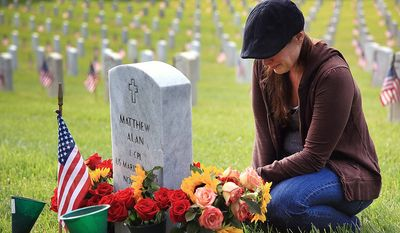 Christina Kaye from Valencia, Calif. weeps over the grave of her two brothers, Mark and Matthew, who died while in military service, during Memorial Day commemoration at the the Los Angeles National Cemetery on Monday May 27, 2013. (AP Photo/Richard Vogel)