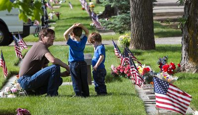 Jim Ransom, of Boise, shows his father's grave site to foster children Matthew, 5, and Nicholas, 3, Monday May 27, 2013 at Dry Creek Cemetery in northwest Boise. Many people celebrated Memorial Day visiting the grave sites of deceased loved ones and decorating the memorials with flowers and flags.