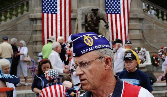 Gary Witt, a two-time Purple Heart recipient for his service in Vietnam during 1968-69 with the Marines, remains at Monument Terrace following the Memorial Day observance to converse with people in the crowd Monday, May 27, 2013 in Lynchburg, Va.  (AP Photo/News & Daily Advance, Sam O'Keefe)