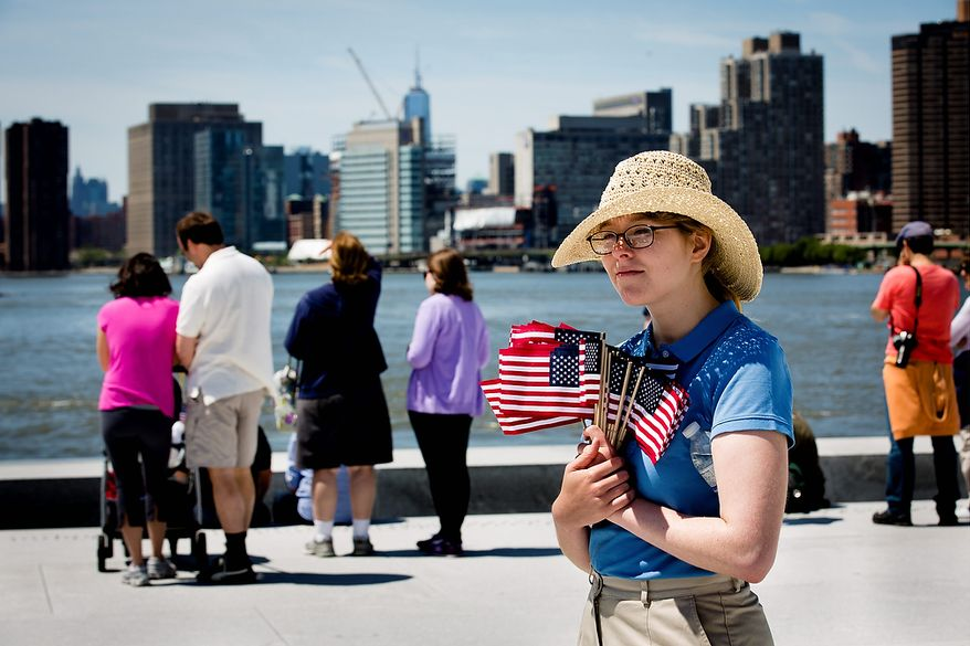 Park ranger Victoria Thompson holds American flags as visitors view the Manhattan skyline after a Memorial Day wreath laying at the Franklin D. Roosevelt Four Freedoms Park on Roosevelt Island, Monday, May 27, 2013, in New York. (AP Photo/John Minchillo)