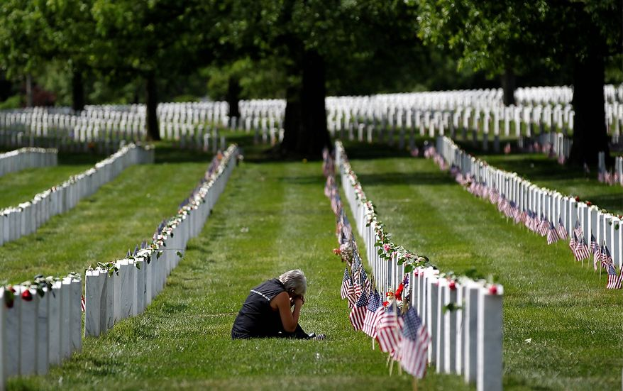 A woman grieves at the grave site of a loved one on Memorial Day at Arlington National Cemetery in Arlington, Va., Monday, May 27, 2013. (AP Photo/Molly Riley)