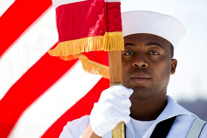Seaman Daniel Odoi of the Navy Operational Support Center of New York City presents the American flag during a Memorial Day wreath laying at the Franklin D. Roosevelt Four Freedoms Park on Roosevelt Island, Monday, May 27, 2013, in New York. (A