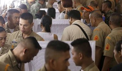 Philippine Marines pay tribute to the flag-draped coffins of seven fellow marines who were killed Saturday in a clash with Abu Sayyaf militants in Jolo, southern Philippines, during the wake at the Philippine Marines headquarters at Fort Bonifacio in Taguig city, east of Manila, Philippines Monday, May 27, 2013. (AP Photo/Bullit Marquez)
