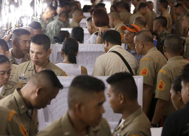 Philippine Marines pay tribute to the flag-draped coffins of seven fellow marines who were killed Saturday in a clash with Abu Sayyaf militants in Jolo, southern Philippines, during the wake at the P