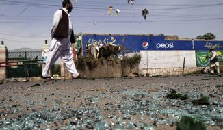 ** FILE ** An Afghan walks on debris after two bombs exploded at a police checkpoint in Jalalabad, Afghanistan, east of Kabul, on Wednesday, May 15, 2013. (AP Photo/Rahmat Gul)
