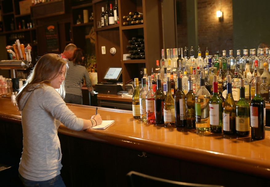 **FILE** Bar manager Maggie Brown takes inventory of wine bottles opened from a week ago at Globe Restaurant on Boylston Street in Boston, the area near the Boston Marathon finish line where two bombs killed three people, on April 23, 2013. (Associated Press/The Boston Globe)