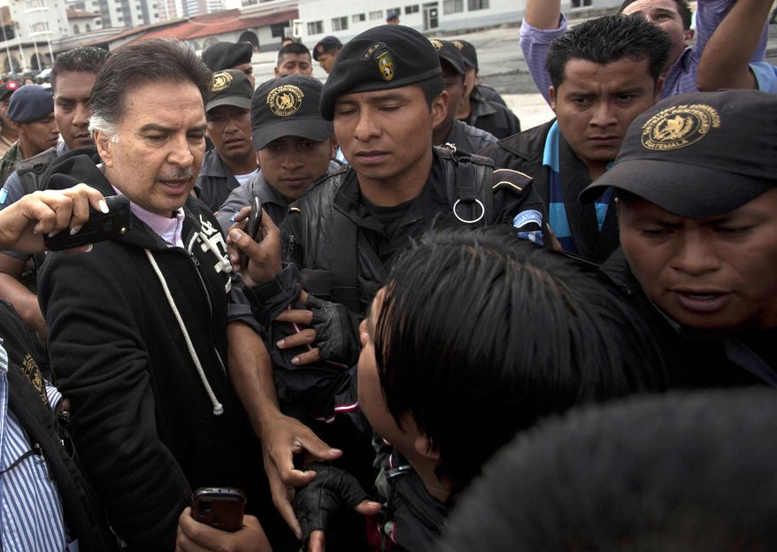 Alfonso Portillo (left), former president of Guatemala, speaks to the press May 24, 2013, as he is led by police to an aircraft that will fly him to the United States from Guatemala City. Portillo was extradited to the United States to face charges of laundering $70 million in Guatemalan funds through U.S. bank accounts. (Associated Press)
