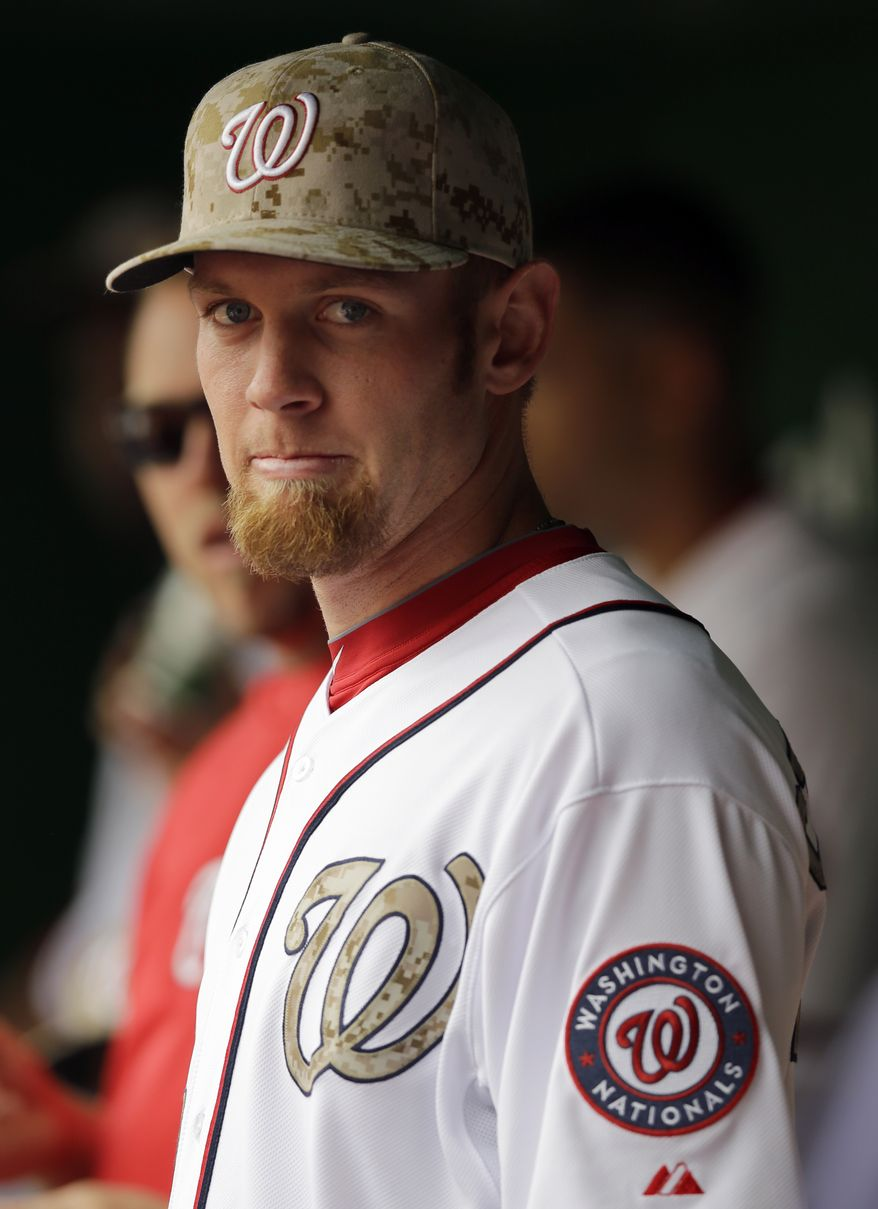 Washington Nationals starting pitcher Stephen Strasburg (37) wears a camouflage hat in the dugout before an interleague baseball game against the Baltimore Orioles at Nationals Park Monday, May 27, 2013, in Washington. (AP Photo/Alex Brandon)