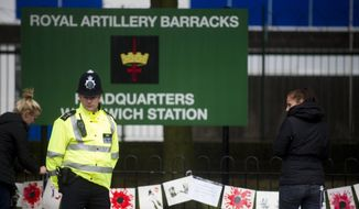 ** FILE ** A police officer stands guard outside the Woolwich Barracks, in London, Friday, May 24, 2013, in response to the bloody attack on Wednesday when a British soldier was killed in the nearby street. (AP Photo/Bogdan Maran)
