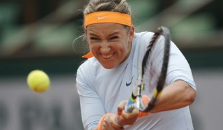 Victoria Azarenka of Belarus returns against Russia's Elena Vesnina in their first round match of the French Open tennis tournament, at Roland Garros stadium in Paris, Wednesday, May 29, 2013. (AP Photo/Christophe Ena)