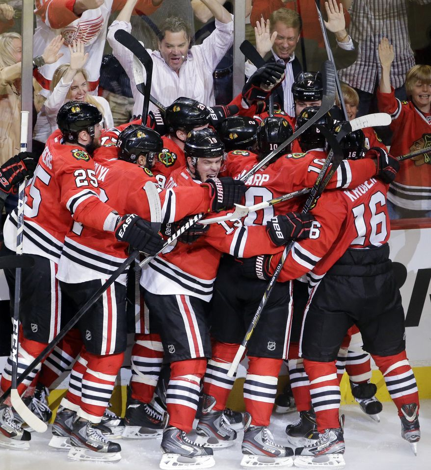 Chicago Blackhawks defenseman Brent Seabrook celebrates with his teammate after scoring a game winning goal during the overtime in Game 7 of the NHL hockey Stanley Cup Western Conference semifinals against the Detroit Red Wings, Wednesday, May 29, 2013, in Chicago. Blackhawks won 2-1. (AP Photo/Nam Y. Huh)