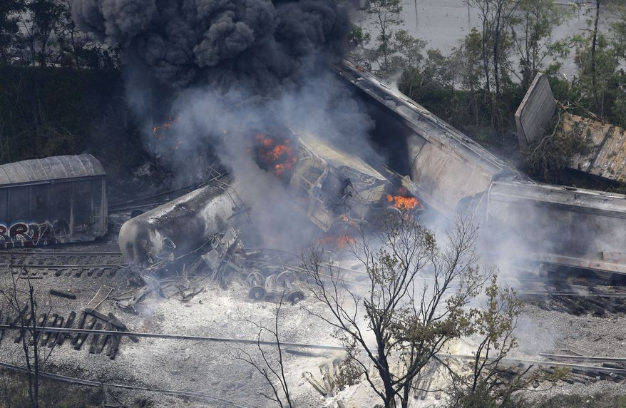 A fire burns at the site of a CSX freight train derailment, Tuesday, May 28, 2013, in Rosedale, Md., where fire officials say the train crashed into a trash truck, causing an explosion that rattled homes at least a half-mile away and collapsed nearby buildings, setting them on fire. (AP Photo/Patrick Semansky)