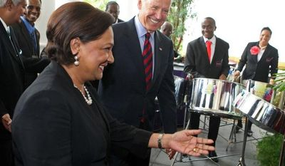 U.S. Vice President Joseph R. Biden, front right, accompanied by Trinidad and Tobago's Prime Minister Kamla Persad-Bissessar, reacts to the sound of the steelpan band, the traditional percussion instrument of the Caribbean twin-island country, upon his arrival to the Diplomatic Center in St. Ann's, Trinidad, Tuesday, May 28, 2013. (AP Photo/Anthony Harris)