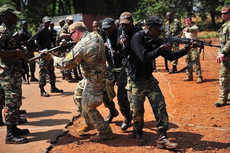 ** FILE ** A U.S. Special Operations Forces service member along with 3rd Bataillon d'Intervention Rapide or Rapid Intervention Battalion (BIR) soldiers demonstrate the proper way to pass hallways and intersections during Close Quarter Battle training during Exercise Silent Warrior 2013 in Bamenda, Cameroon Jan. 17, 2013. (Image: Africom.mil, Air Force Master Sgt. Larry W. Carpenter Jr.)