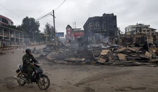 A man rides a motorcycle near a burned building that housed an orphanage for Muslim children in Lashio, northern Shan State, Myanmar, on May 30, 2013. Many Buddhists and Muslims stayed locked inside their homes and shops were shuttered after two days of violence in Lashio town, near the border with China, the latest region to fall prey to the country's spreading sectarian violence. (Associated Press)