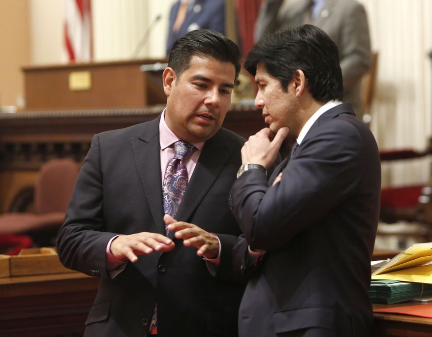 Democratic state Sens. Ricardo Lara (left) and Kevin de Leon converse during a Senate session at the Capitol in Sacramento, Calif., on Wednesday, May 29, 2013. By a 27-9 vote the Senate approved Mr. Lara's bill that would use California's tax policy in an attempt to pressure the Boys Scouts of America into fully accepting gay members. The bill, SB323, gets rid of a tax exemption for sales and use taxes, as well as corporate taxes, for youth groups that discriminate. (AP Photo/Rich Pedroncelli)
