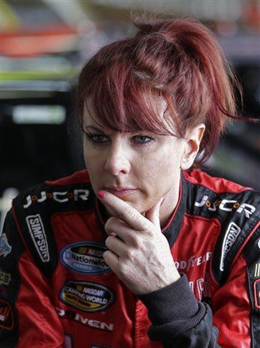 Jennifer Jo Cobb looks out of the garage area before practice for the NASCAR Truck series North Carolina Education Lottery 200 auto race at Charlotte Motor Speedway in Concord, N.C., Thursday, May 16, 2013. (Associated Press)