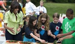 First lady Michelle Obama, left, gives instructions to students from Long Beach Island Grade School in Ship Bottom, N.J., as they make a pizzas made from the summer crop harvested from the White House kitchen garden, Tuesday, May 28, 2013, at the White House in Washington. (Associated Press)