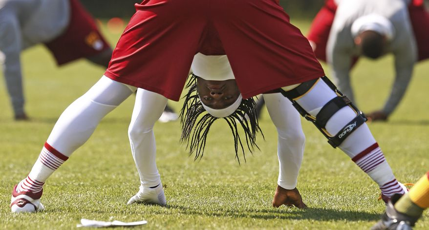 Washington Redskins quarterback Robert Griffin III (10) stretches at practice during a NFL football organized team activity at Redskins Park in Ashburn, Va., Thursday, May 30, 2013. (AP Photo/Charles Dharapak)