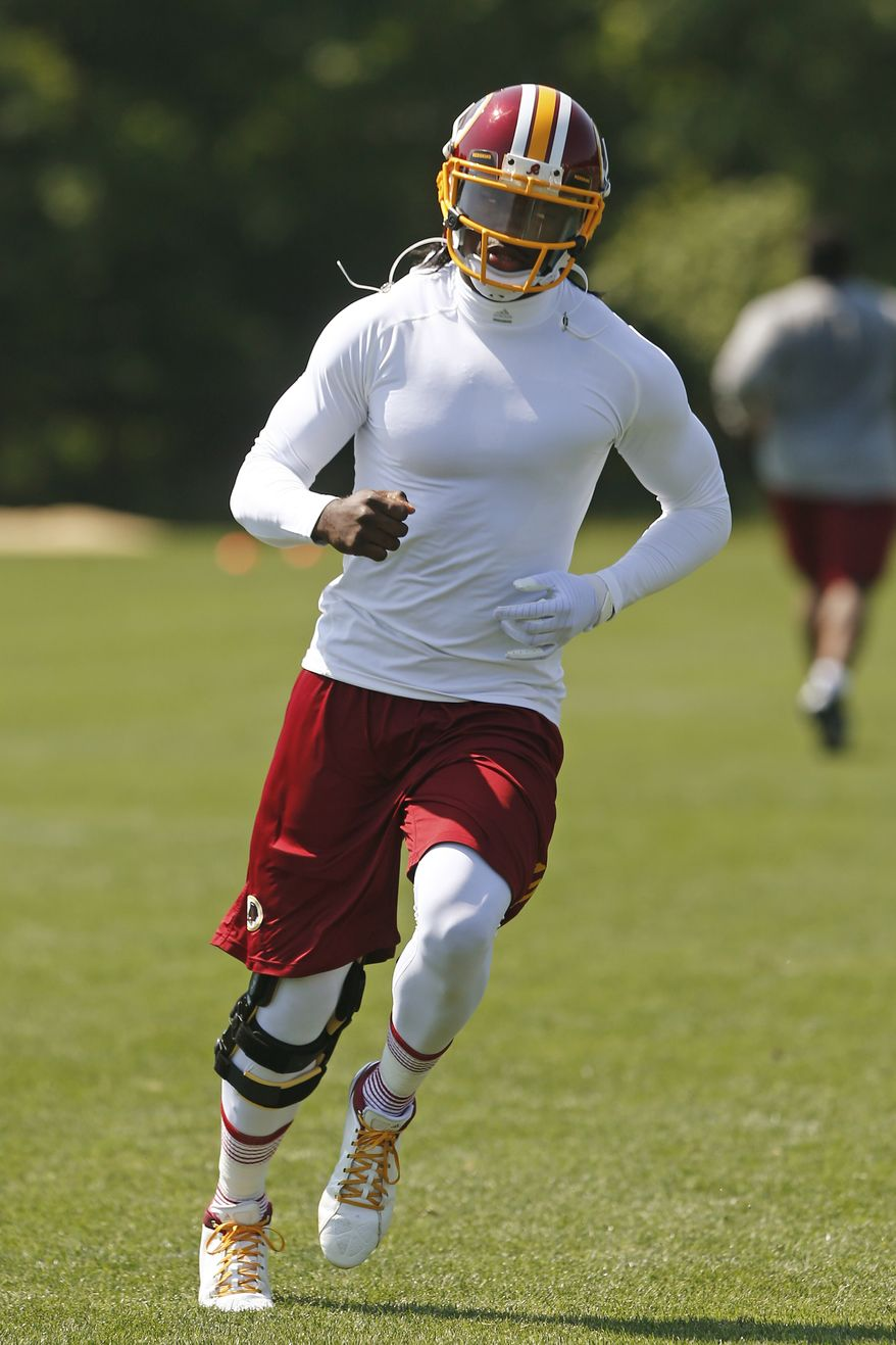 Washington Redskins quarterback Robert Griffin III (10) runs at practice during an NFL football organized team activity at Redskins Park in Ashburn, Va., Thursday, May 30, 2013. (AP Photo/Charles Dharapak)