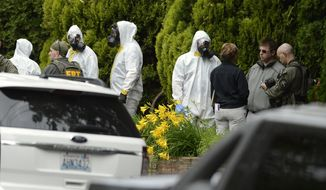 **FILE** During the execution of a search warrant, members of the joint federal hazmat team, FBI and local law enforcement gather in front of the Osmun Apartments in Spokane, Wash., on May 18, 2013. The search warrant is in connection with ricin-laced letters intercepted at a Post Office facility in Spokane earlier in the week. (Associated Press/TheSpokesman-Review)