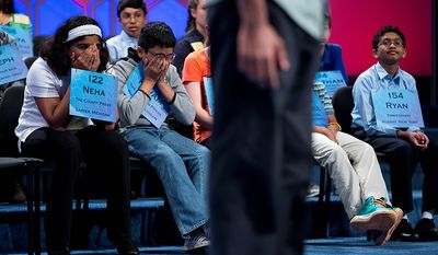 Neha Seshadri, 12, of Imlay City, Mich., left, Kuvam Shahane, 13, of Rochester Hills, Mich., center, and Ryan Devanandan, 13, of Albany, N.Y., right, listen as Anuk Dayaprema, 14, of Vincenza, Italy spells during the semifinal round of the National Spelling Bee, Thursday, May 30, 2013, in Oxon Hill, Md. (AP Photo/Evan Vucci)