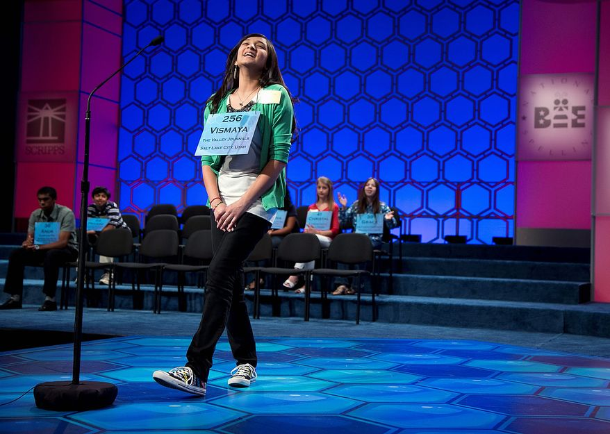 "Vismaya Kharkar, 14, of Bountiful, Utah, reacts after spelling the word ""agelicism"" correctly during the semifinal round of the National Spelling Bee on Thursday, May 30, 2013, in Oxon Hill, Md. (AP Photo/Evan Vucci)"