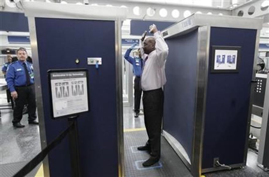 Volunteers pass through the first full body scanner, which uses backscatter technology, at O'Hare International Airport in Chicago on March 10, 2010. Those airport scanners with their all-too revealing body images will soon be going away. The Transportation Security Administration says the X-ray scanners will be gone by June 2013 because the company that makes them can't fix the privacy issues. (Associated Press)