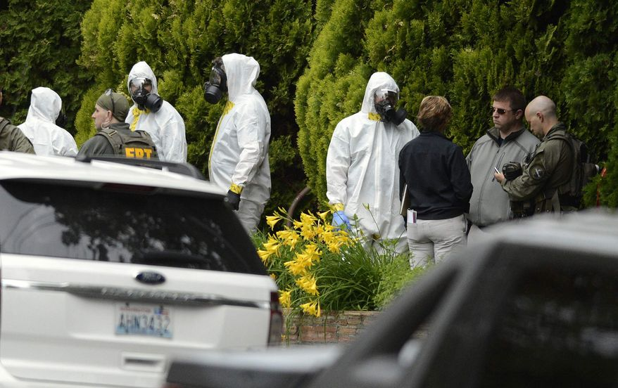 ** FILE ** In this May 18, 2013, file photo, members of the Joint Federal Haz-Mat Team, FBI, and local law enforcement gather in front of the Osmun Apartments near the intersection of First Avenue and Oak Street in Browne's Addition during the execution of a search warrant, in Spokane, Wash. The search warrant is in connection with ricin-laced letters intercepted at a Post Office facility in Spokane earlier in the week. (AP Photo/The Spokesman-Review, Colin Mulvany)