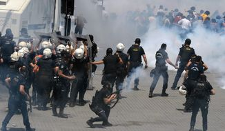 Riot police clash with demonstrators after they used tear gas and pressurized water in a dawn raid on May 31, 2013, to rout a peaceful demonstration by hundreds of people staging a sit-in to prevent the uprooting of trees at a park in Istanbul. (Associated Press)