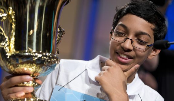 "Arvind Mahankali, 13, of Bayside Hills, N.Y., holds the championship trophy after he won the National Spelling Bee by spelling the word ""knaidel"" correctly on Thursday, May 30, 2013, in Oxon Hill, Md. (AP Photo/Evan Vucci)"