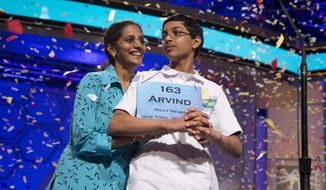 "Arvind Mahankali, 13, of Bayside Hills, N.Y., is congratulated by his mother Bhavani, as confetti falls after he won the National Spelling Bee by spelling the word ""knaidel"" correctly on Thursday, May 30, 2013, in Oxon Hill, Md. (AP Photo/Evan Vucci)"