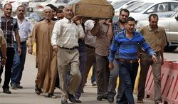 ** FILE ** Mourners carry the coffin of a man killed in a liquor store attack in Baghdad, Iraq, May 15, 2013. More than a year after the U.S. military left Iraq, the country is reeling from its most sustained violence since 2008. Over the last two months more than 1,200 people have been killed, raising fears the country is sliding back into chaos. (Associated Press)