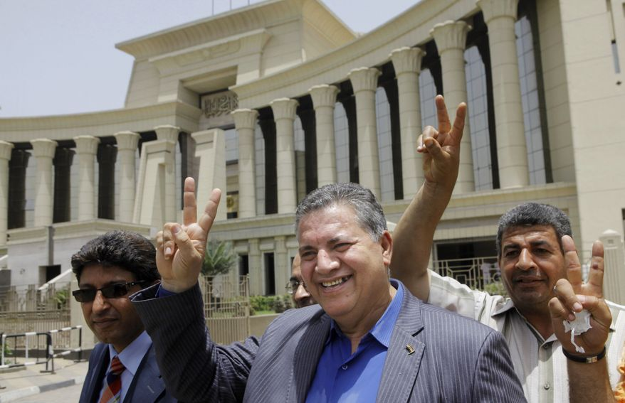 Hamdy El-Fakharany (center), an opposition leader and former member of the now-dissolved Parliament, and other activists flash victory signs in front of the Supreme Constitutional Court in Cairo on Sunday, June 2, 2013. The high court ruled that the nation's Islamist-dominated legislature and constitutional panel were illegally elected and that the legislature's upper house, the only one currently sitting, must be dissolved when parliament's lower chamber is elected later this year or early in 2014. (AP Photo/Amr Nabil)