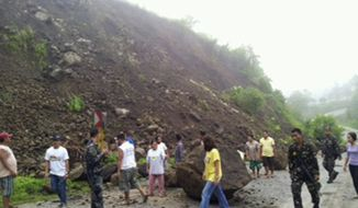 Residents of North Cotabato province in the southern Philippines look at boulders that partially blocked a highway on Sunday, June 2, 2013, after a magnitude-5.7 earthquake hit late Saturday. (AP Photo/North Cotabato Provincial Office)