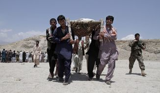 Afghan men carry the bodies of 7 civilians killed, by a roadside bomb in the Alingar district of Laghman province, east of Kabul, Afghanistan, Monday, June 3, 2013. A statement from the provincial government said a group of four women and two children had gone with a male driver into the hills to collect firewood. On their way back, their vehicle hit the mine and all inside were killed. (AP Photo/Rahmat Gul)