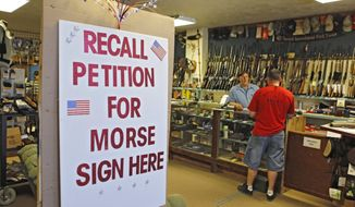 **FILE** A large sign posted at the entrance of Paradise Firearms in Colorado Springs, Colo., invites customers to sign a recall petition against Colorado Democratic State Senate President John Morse on May 24, 2013. In gun-friendly Colorado, gun-rights activists with support of the National Rifle Association are seeking Morse's ouster for his support of new laws that restrict ammunition magazines and expand background checks to private gun sales. (Associated Press)