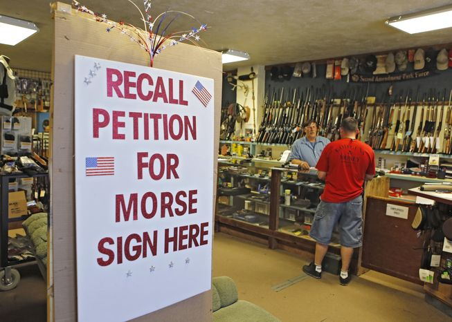 **FILE** A large sign posted at the entrance of Paradise Firearms in Colorado Springs, Colo., invites customers to sign a recall petition against Colorado Democratic State Senate President John Morse on May 24, 2013. In gun-friendly Colorado, gun-rights activists with support of the National Rifle Association are seeking Morse's